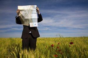 Homme d'affaires lisant une carte dans un champ